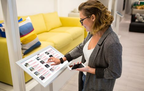 Woman configured on self-service screen product next to a yellow couch