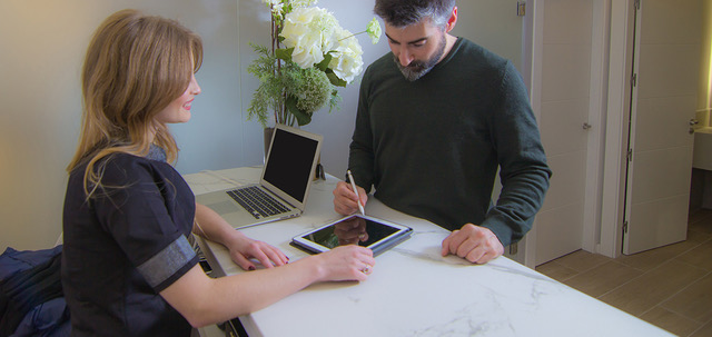Woman and man drawing with pen on a tablet