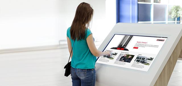 Frau informiert sich an großem Bildschirm